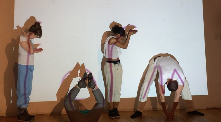 Four actors bend their bodies to form letters