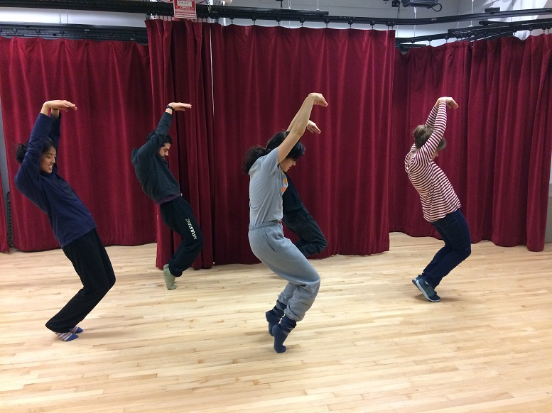 four actors bend their bodies into s-shapes to form letters