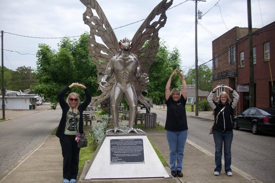 Tourists posing with the Moth Man Statue in Point Pleasant, West Virginia