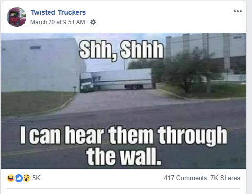 "A semi with its cab turned at a 90 degree angle against the wall of a building with the words"" Sh, I can hear them through the wall"""