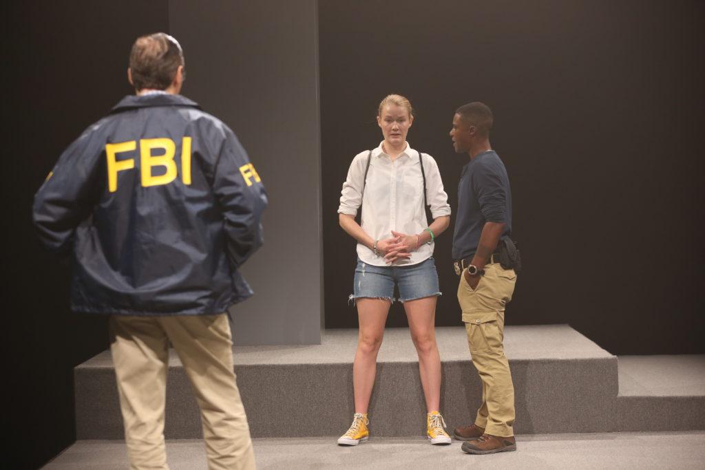 Agent Garrick (Pete Simpson) and Agent Taylor (TL Thompson) corner Reality Winner (Emily Davis).